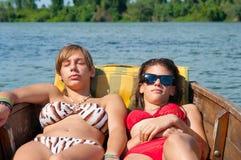 Adolescentes mignonnes s'exposant au soleil dans le bateau Image libre de droits
