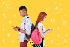 Adolescentes modernos que se colocan de nuevo a la parte posterior y que usan sus smartphones modernos Fotos de archivo