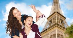 Adolescentes montrant la paix au-dessus de Tour Eiffel Photographie stock libre de droits