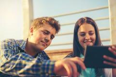 Adolescentes muchacha y muchacho en banco usando la tableta de Digitaces Imagen de archivo
