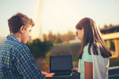 Adolescentes muchacha y muchacho que usa el ordenador portátil al aire libre Fotos de archivo