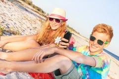 Adolescentes (muchacho y muchacha) usando el teléfono elegante y la música que escucha Fotografía de archivo