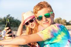 Adolescentes (muchacho y muchacha) usando el teléfono elegante y la música que escucha Imagen de archivo