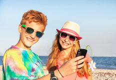 Adolescentes (muchacho y muchacha) usando el teléfono elegante y la música que escucha Fotos de archivo libres de regalías