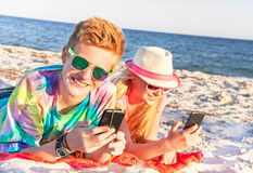 Adolescentes (muchacho y muchacha) usando el teléfono elegante y la música que escucha Imagenes de archivo