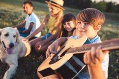 Adolescentes multiétnicos con la guitarra Foto de archivo libre de regalías