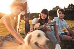Adolescentes multiétnicos con la guitarra Fotografía de archivo libre de regalías