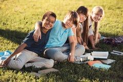 Adolescentes multiétnicos que estudian en parque Fotos de archivo
