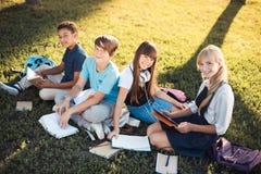 Adolescentes multiétnicos que estudian en parque Foto de archivo