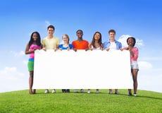 Adolescentes Multi-étnicos al aire libre que sostienen la cartelera para el espacio de la copia Foto de archivo