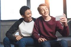 Adolescentes multiculturales felices que hacen la llamada video con smartphone y que se sientan en el sofá en casa Fotos de archivo libres de regalías