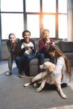 Adolescentes multiculturales felices que juegan a los videojuegos con las palancas de mando en casa Foto de archivo libre de regalías