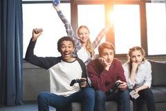 Adolescentes multiculturales felices que juegan a los videojuegos con las palancas de mando en casa Fotografía de archivo libre de regalías