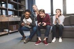 Adolescentes multiculturales felices que juegan a los videojuegos con las palancas de mando en casa Imagen de archivo libre de regalías