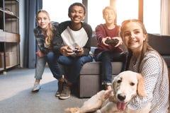 Adolescentes multiculturales felices que juegan a los videojuegos con las palancas de mando en casa Imagen de archivo