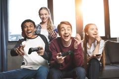 Adolescentes multiculturales felices que juegan a los videojuegos con las palancas de mando en casa Fotos de archivo