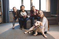 Adolescentes multiculturales felices que juegan a los videojuegos con las palancas de mando en casa Fotografía de archivo
