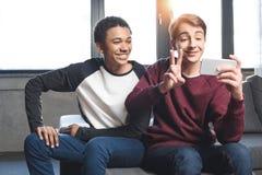 Adolescentes multiculturales felices que toman el selfie en smartphone y que se sientan en el sofá en casa Fotos de archivo
