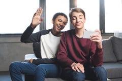 Adolescentes multiculturales que hacen la llamada video con smartphone y que se sientan en el sofá en casa, adolescentes que tien Imagen de archivo libre de regalías