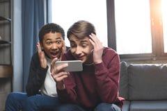 Adolescentes multiculturales que hacen la llamada video con smartphone y que se sientan en el sofá en casa, adolescentes que tien Fotos de archivo libres de regalías