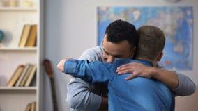 Adolescentes multirraciales que componen después de la pelea, abrazo sonriente feliz de los amigos almacen de video