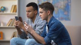 Adolescentes multirraciales que juegan a juegos en los smartphones, ignorando la comunicación viva metrajes