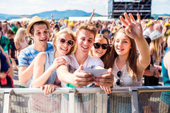 Adolescentes no festival de música do verão na multidão que toma o selfie Imagem de Stock Royalty Free