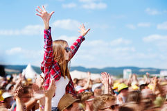 Adolescentes no festival de música do verão que apreciam-se