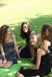 Adolescentes novos de sorriso que relaxam no parque fotos de stock
