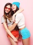 Adolescentes o amigos bonitos sonrientes felices que abrazan sobre rosa Imágenes de archivo libres de regalías