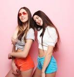 Adolescentes o amigos bonitos sonrientes felices que abrazan sobre rosa Foto de archivo libre de regalías