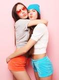 Adolescentes o amigos bonitos sonrientes felices que abrazan sobre rosa Imagenes de archivo