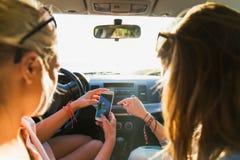 Adolescentes o mujeres con smartphone en coche Imagen de archivo libre de regalías