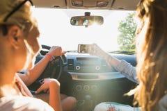 Adolescentes o mujeres con smartphone en coche Foto de archivo