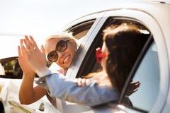 Adolescentes o mujeres felices en coche en la playa Imagen de archivo