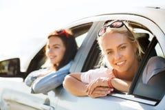 Adolescentes o mujeres felices en coche en la playa Imagen de archivo libre de regalías
