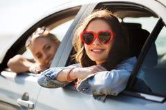 Adolescentes o mujeres felices en coche en la playa Fotografía de archivo libre de regalías