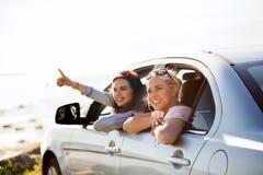 Adolescentes o mujeres felices en coche en la playa Fotos de archivo libres de regalías