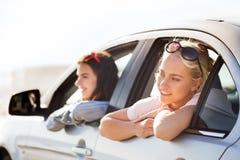 Adolescentes o mujeres felices en coche en la playa Imagenes de archivo