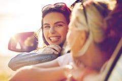 Adolescentes o mujeres felices en coche en la playa Imágenes de archivo libres de regalías