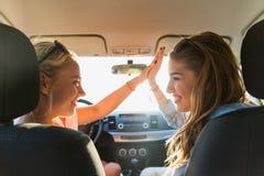 Adolescentes o mujeres felices que conducen en coche Imagen de archivo