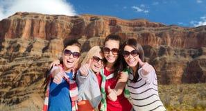 Adolescentes o mujeres jovenes que muestran los pulgares para arriba Imagen de archivo libre de regalías