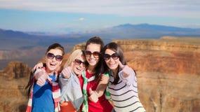 Adolescentes o mujeres jovenes que muestran los pulgares para arriba Imágenes de archivo libres de regalías