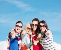 Adolescentes o mujeres jovenes que muestran los pulgares para arriba Imagenes de archivo