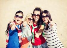 Adolescentes o mujeres jovenes que muestran los pulgares para arriba Imagen de archivo