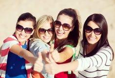Adolescentes o mujeres jovenes que muestran los pulgares para arriba Fotografía de archivo