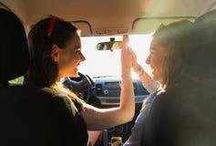 Adolescentes ou femmes heureuses conduisant dans la voiture Photos stock