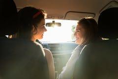 Adolescentes ou femmes heureuses conduisant dans la voiture Image stock