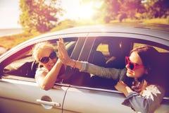 Adolescentes ou femmes heureuses dans la voiture au bord de la mer Photo stock
