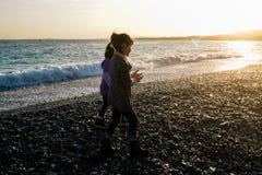 Adolescentes por el mar en la puesta del sol Imagen de archivo